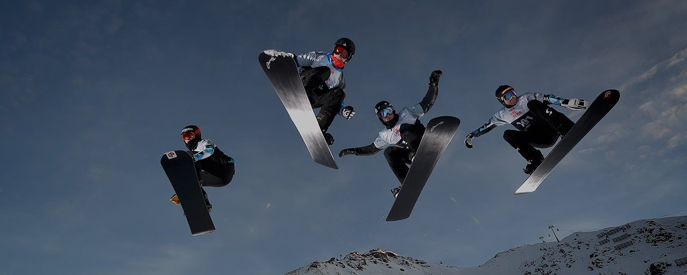 Four people leap through the air on snowboards.